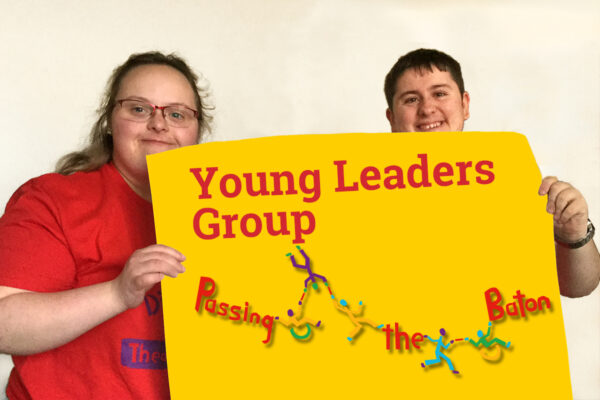 """Photo of 2 of DIY's young leaders holding up a piece of paper with """"Young Leaders Group"""" and the 'Passing the Baton' logo"""